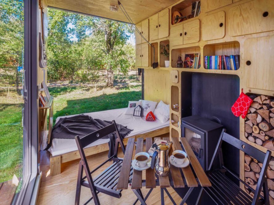 bed, patio table and fireplace inside tiny home