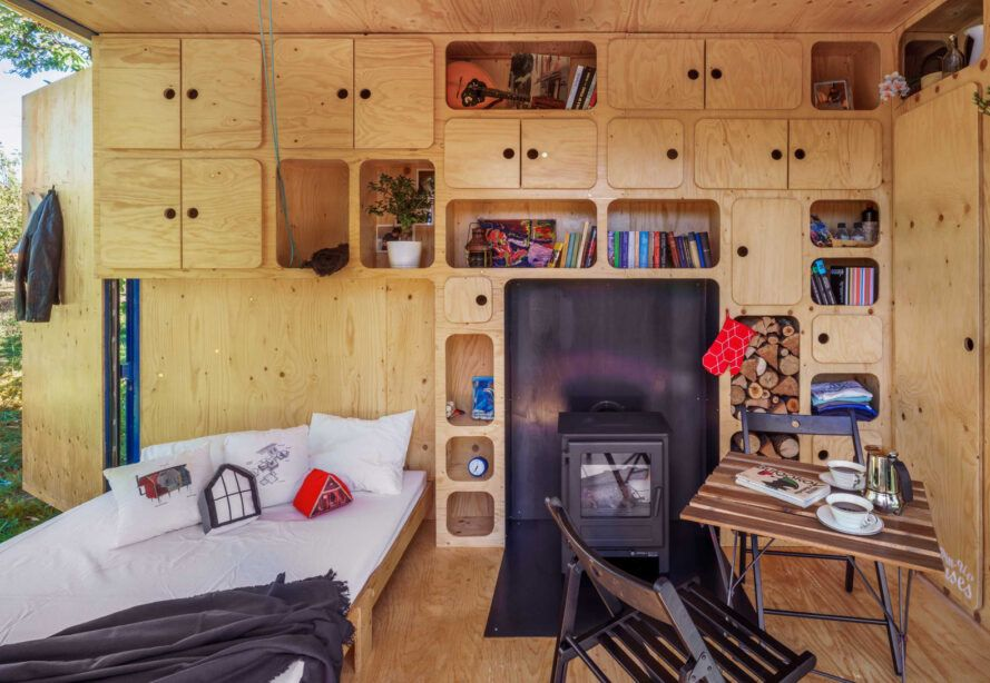 wooden tiny home interior with bed near fireplace