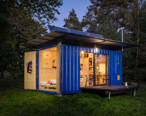 blue container home with wood patio and solar panels