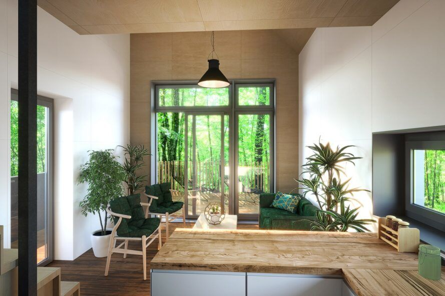 An interior room with simple wood counters, furniture and a glass door looking out on a green forest.
