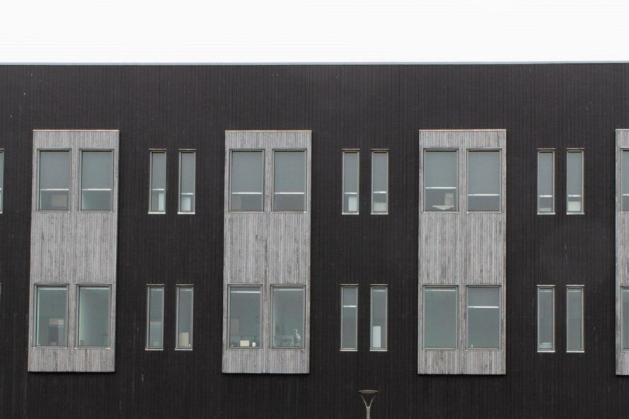 close-up of gray and black building with small windows