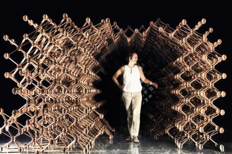A person emerging from a dark tunnel of interconnected parts that form Plexus.