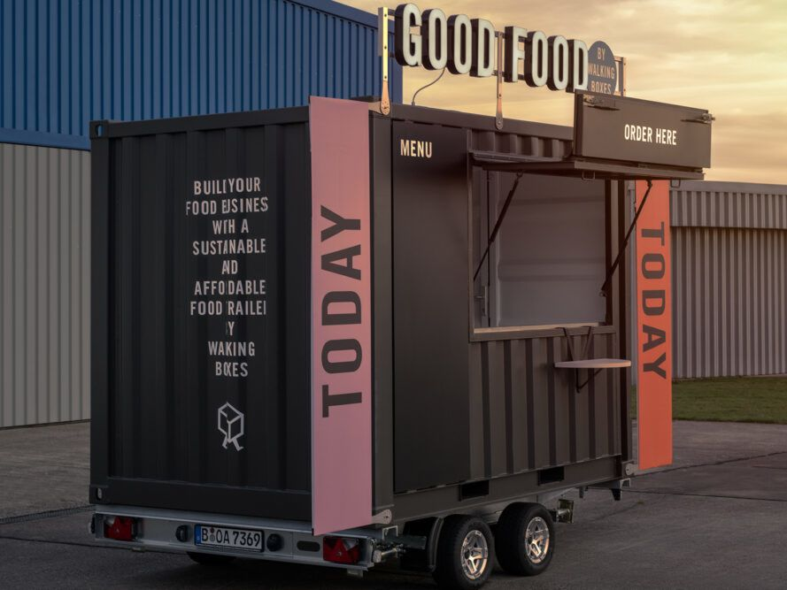 at dusk the black food cart has pink and orange signs