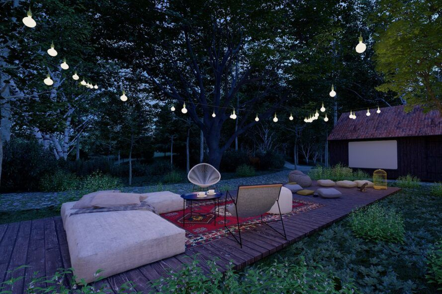 A backyard with a wood deck area featuring a rug, chair, sitting cushions and string lights.