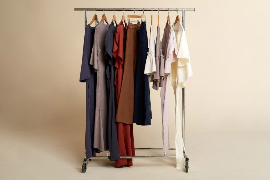 A rack of clothes against an off-white background.