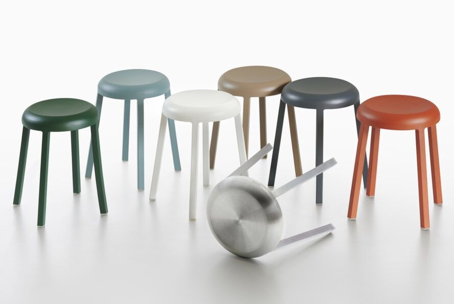 A display of colorful stools, with an aluminum stool tipped over in front of the bunch.