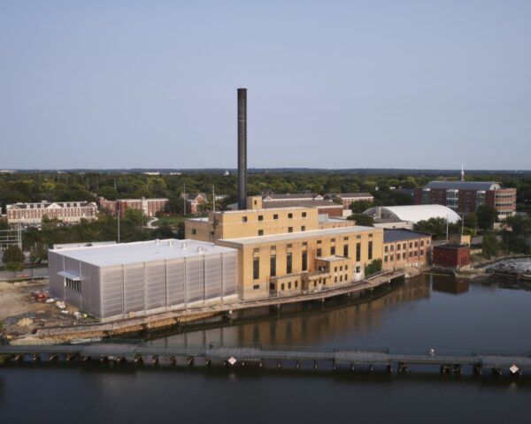 A multi-building front with facades of yellow paint and polycarbonate. A tall smokestack chimney sticks out from the roof. In front of the building is a river.
