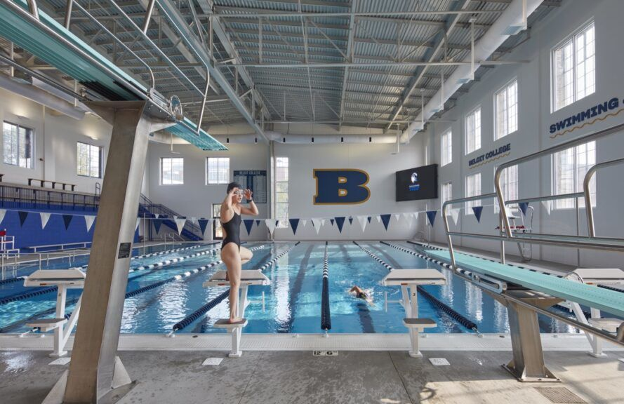 An indoor eight-lane swimming pool with a person getting ready to dive in to the water.
