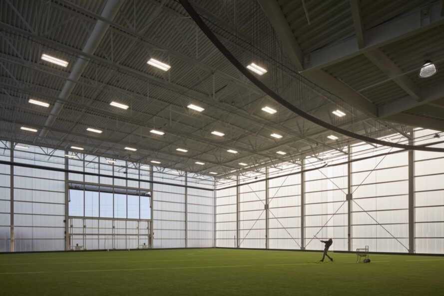 An indoor turf field with a person standing on it.