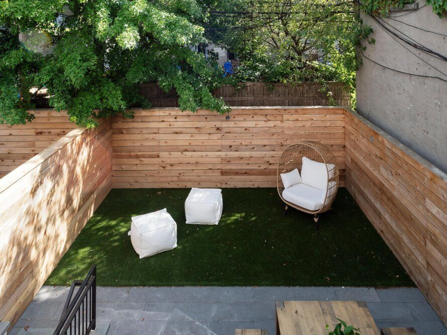 rooftop patio with white chairs surrounded by wood walls