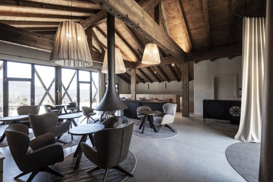 round tables and plush dining chairs in room with exposed wood ceiling