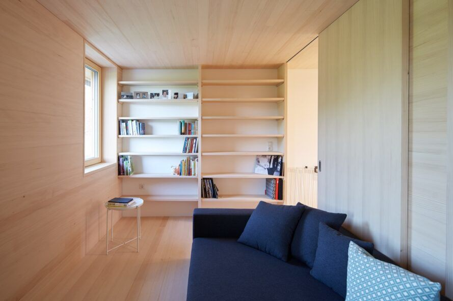 wood-lined living room with blue sofa and built-in shelves