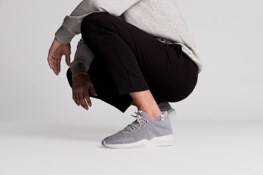 The bottom half of a person crouching while wearing a pair of gray sneakers.