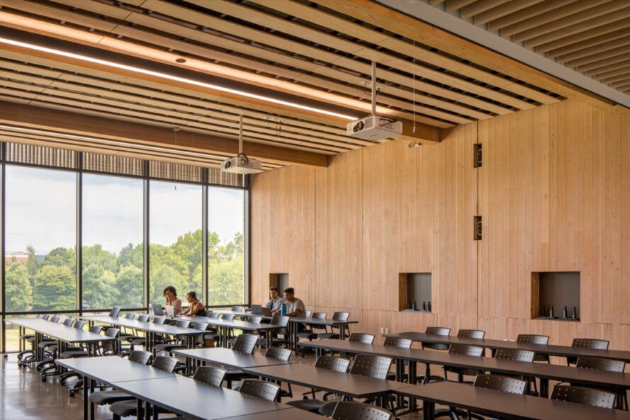 long tables in room with wood walls and ceilings and one end wall of glass