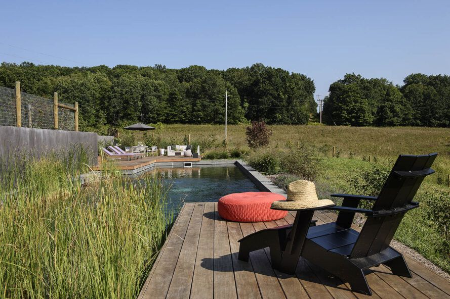 A wooden deck with a black chair and red cushion, all of which is in front of a long rectangular natural pool.