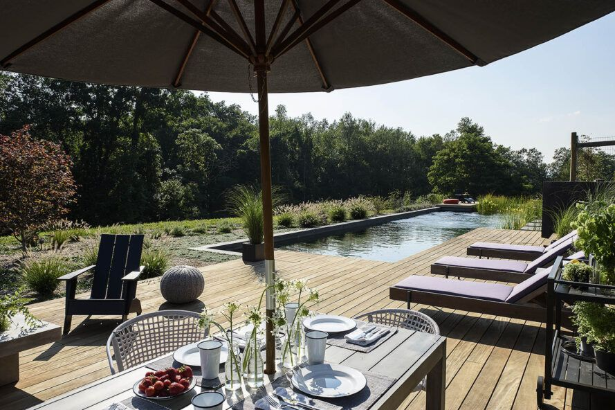 A wooden deck with pool chairs, a table and an umbrella, all of which is in front of a long rectangular natural pool.