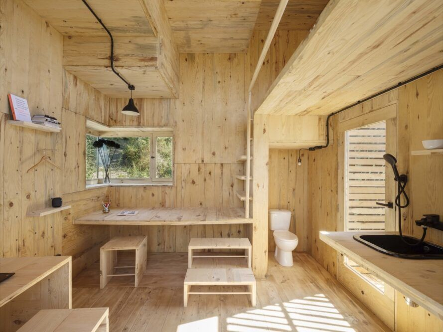 raw wood cabin interior with built-in desk and small toilet cubby