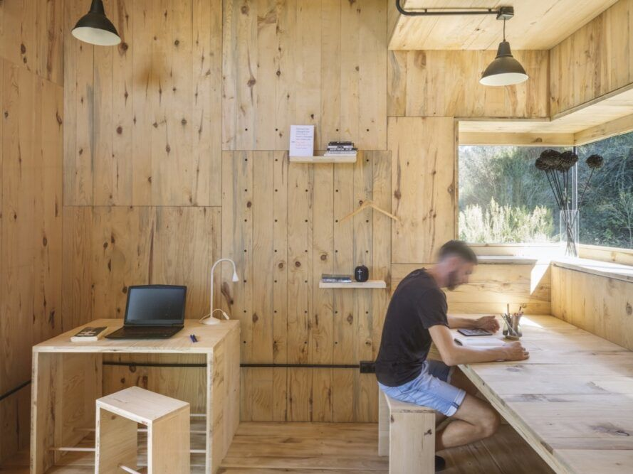 person writing while sitting at long wood desk