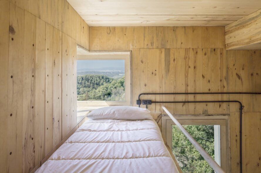 elevated bed near large window overlooking forest