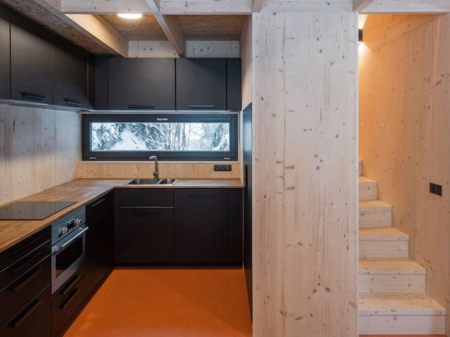 kitchen with raw wood walls and black cabinets