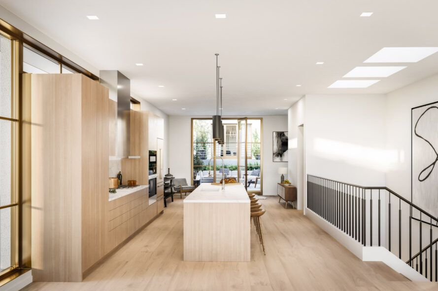 kitchen with long island facing wall of light wood cabinets
