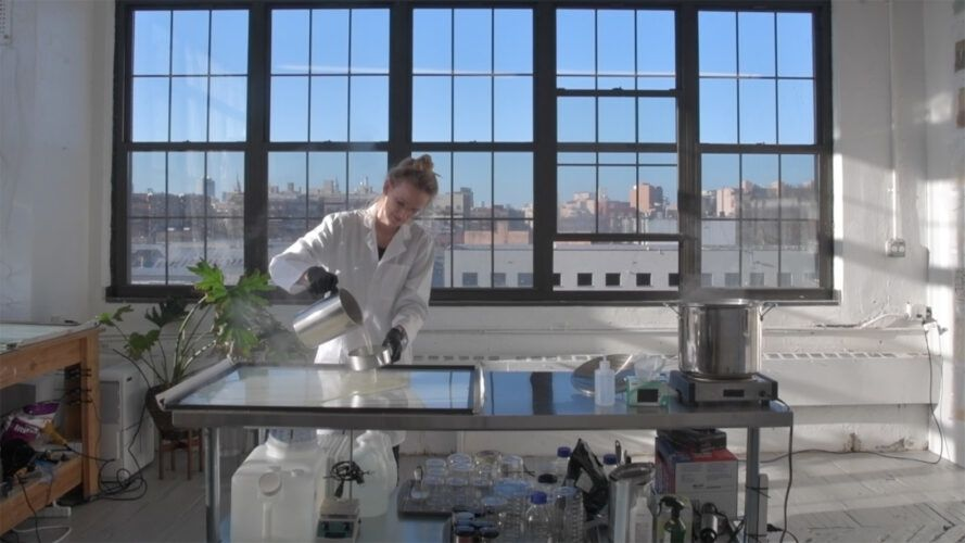 person pouring liquid in a lab setting