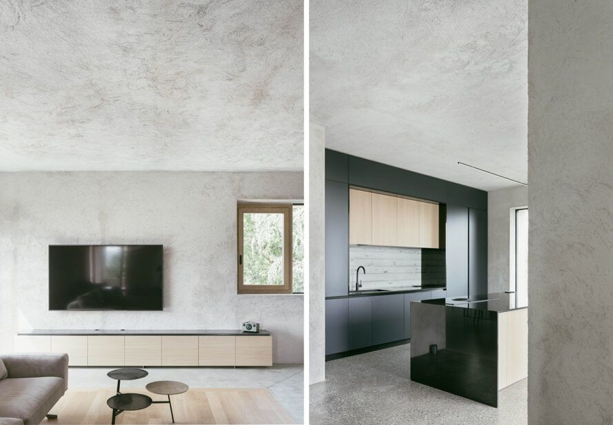 On the left, wall-mounted TV in room with raw concrete walls, floors and ceilings. On the right, kitchen with black cabinets.