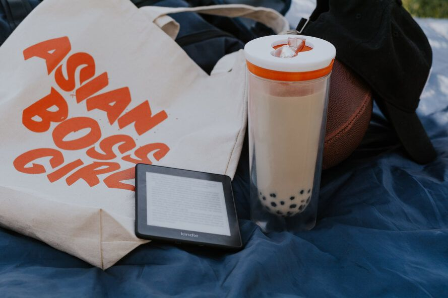 """From left to right, an off-white tote bag with orange letters reading """"Asian Girl Boss,"""" a Kindle and a reusable boba cup."""