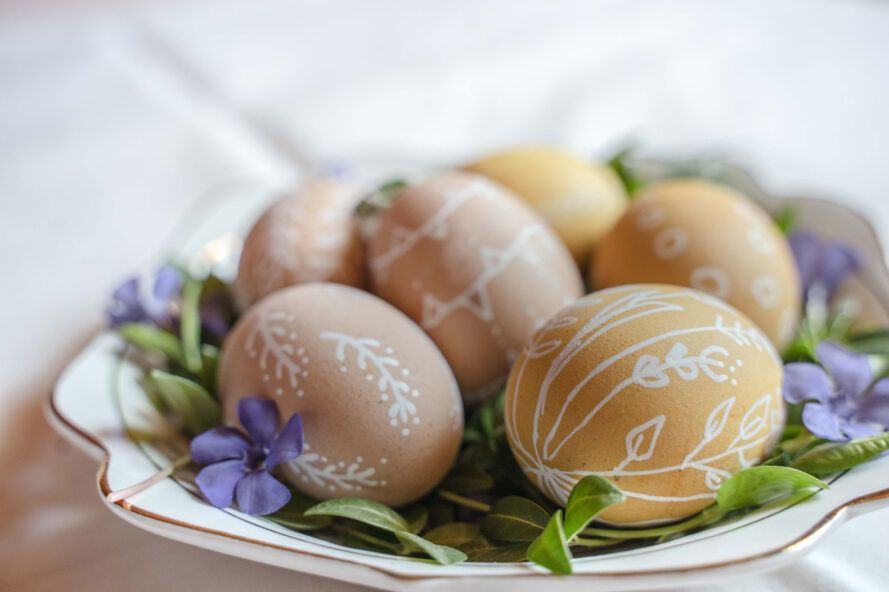 naturally dyed eggs with white floral drawings