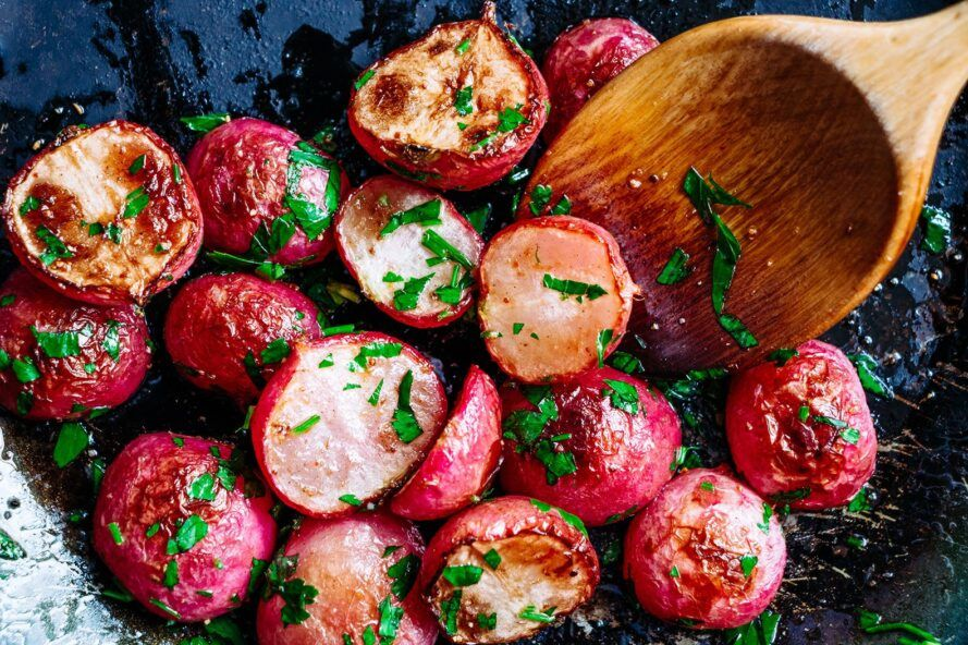 wood spoon scooping up roasted radishes