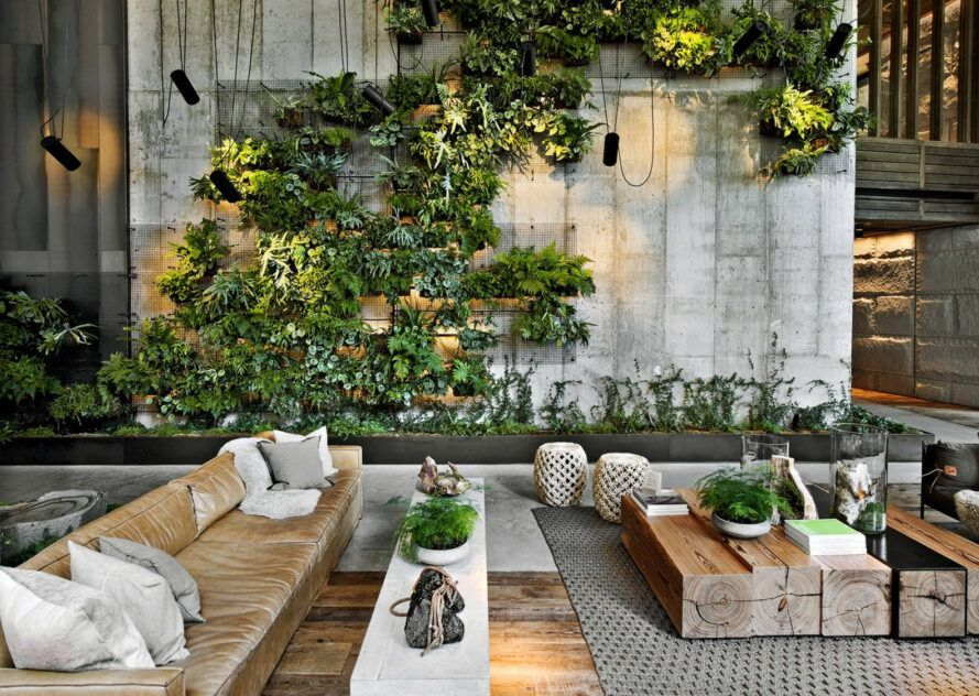 An outdoor sitting area framed by a large green wall of plants.