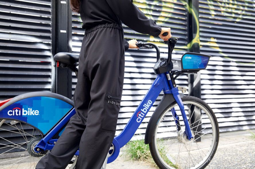 person walking with bike while wearing black jumpsuit