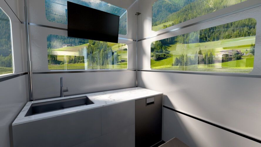 small kitchen area and mounted TV inside a pop-up camper