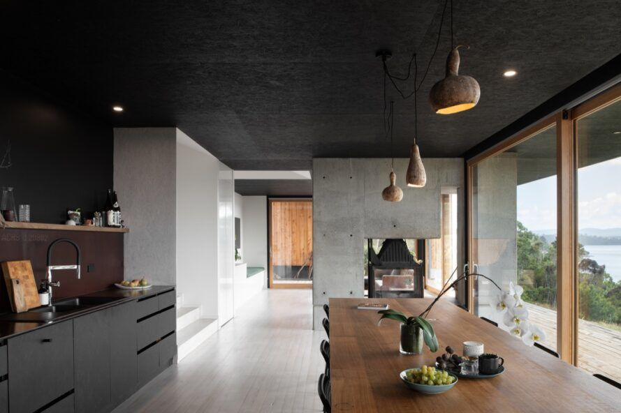 kitchen with black cabinets next to long, dark wood dining table