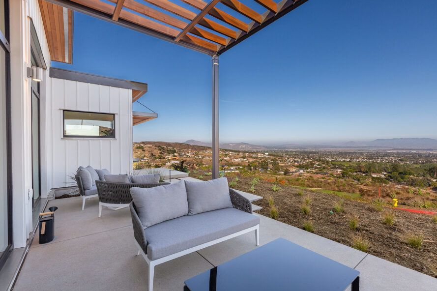 gray patio seat and black table on outdoor patio overlooking desert landscape