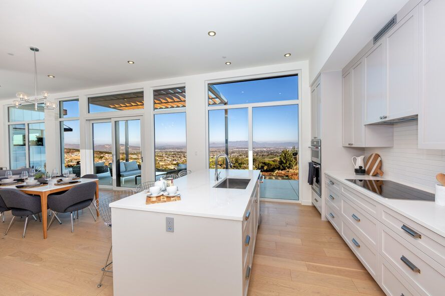 white kitchen with large island near wall of glass