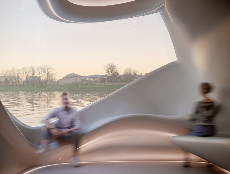 people sitting on built-in bench inside a pod floating on a river