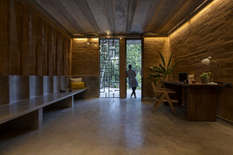 concrete bench built into rammed earth wall across from a wood desk