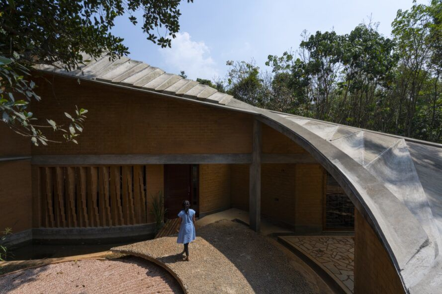 person walking toward rammed earth home with sloped roof