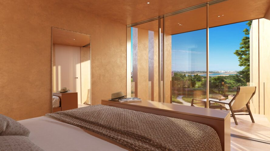 large bed facing wall of glass with ocean views