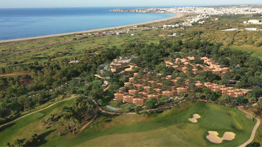 aerial view of hotel suites and golf course near ocean