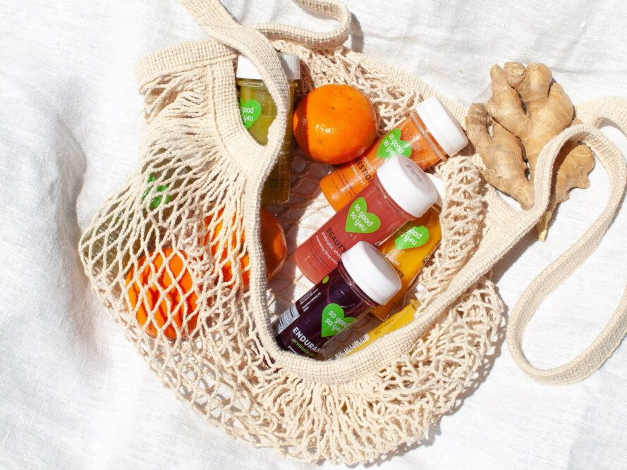 fresh fruit and bottles of juice in a cloth bag