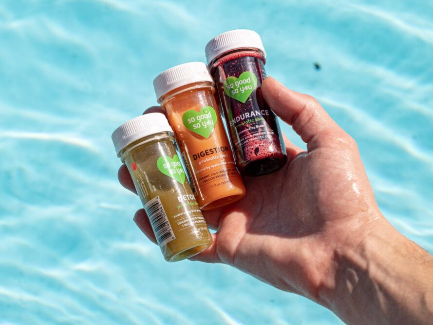 hand holding cold-pressed juices by a pool