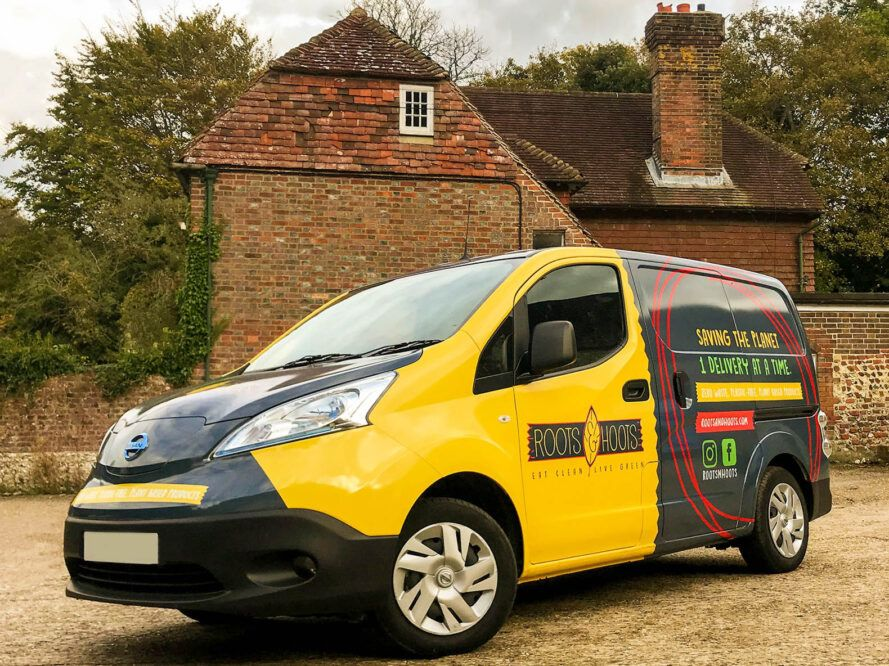 A yellow electric van with Roots and Hoots info on the side.