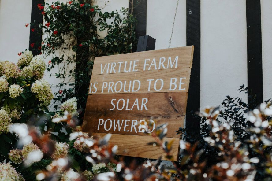 """wood sign that reads, """"Virtue Farm is proud to be solar powered"""""""