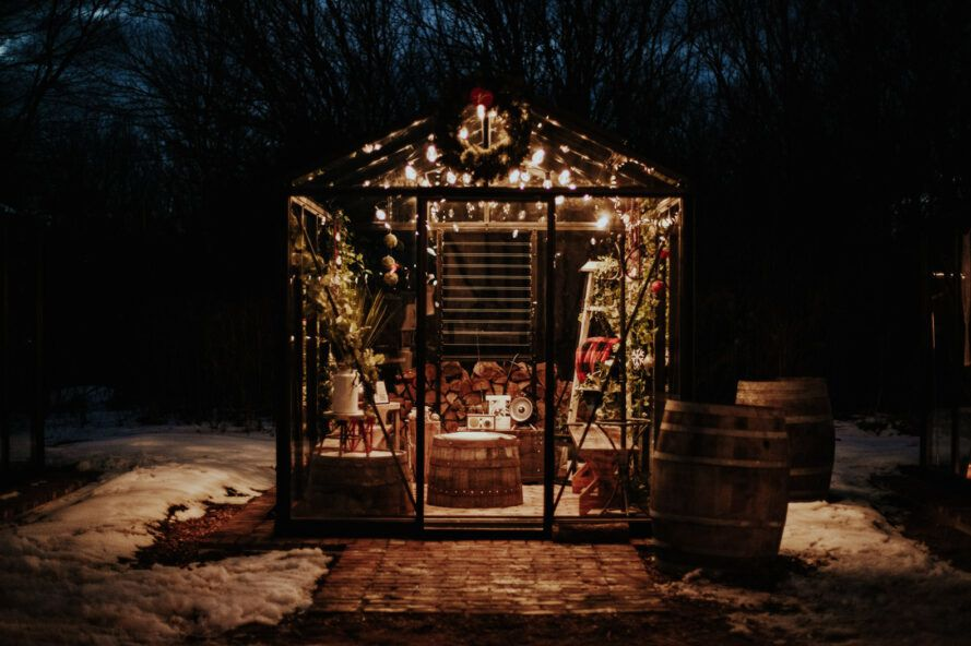 glass greenhouse lit up with string lights at night