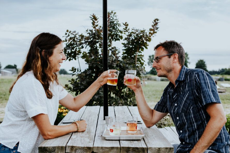 two people drinking hard cider