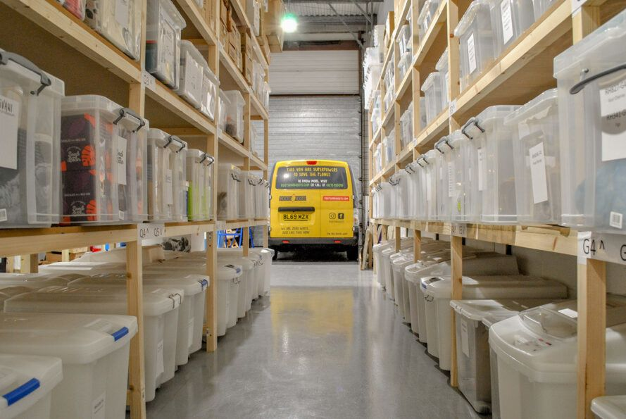 A warehouse with wood shelves and a yellow van.