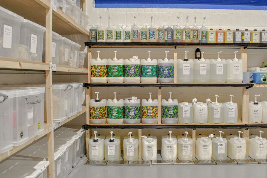 A warehouse with wood shelves with large refill containers.