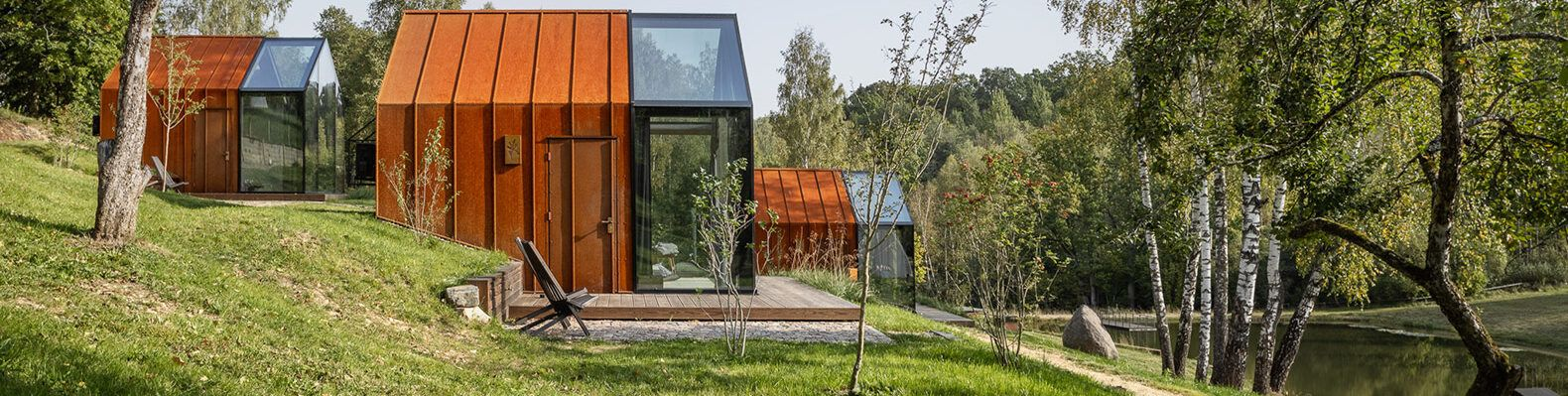 glass and weathered steel cabins on a hill